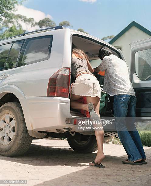 young couple loading boot of 4x4, rear view - long legs short skirts stock photos and pictures