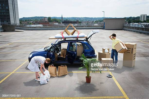 young couple loading boxes and bags into car on rooftop carpark - domestic car stock pictures, royalty-free photos & images