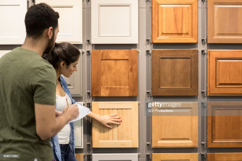 Young couple look at cabinet samples in home improvement store : Stock Photo