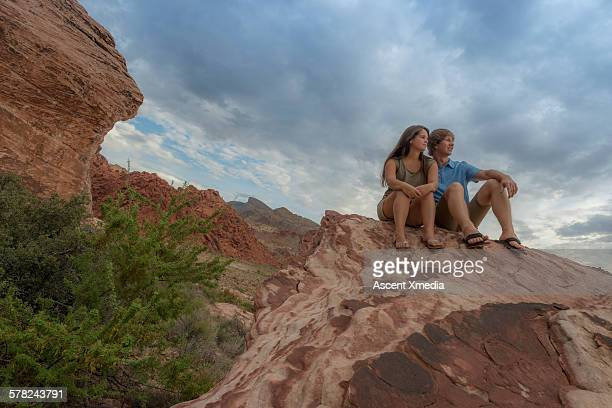Young couple look out across desert landscape