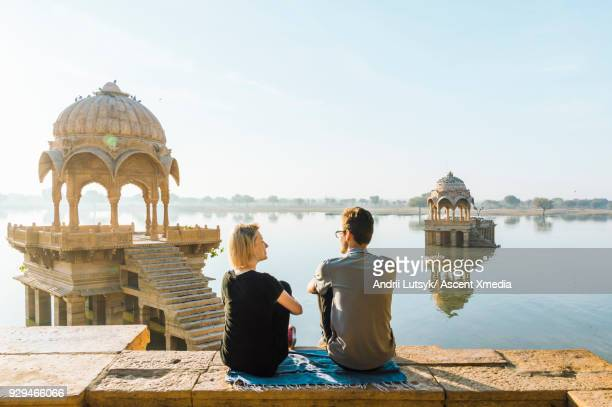 Young couple look out at Gadi Sagar lake in morning light