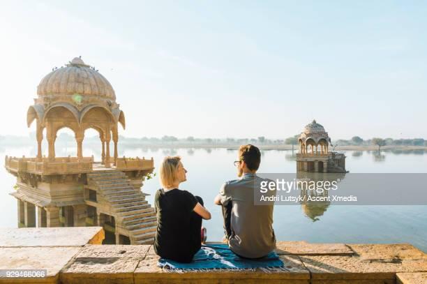 young couple look out at gadi sagar lake in morning light - look back at early colour photography imagens e fotografias de stock