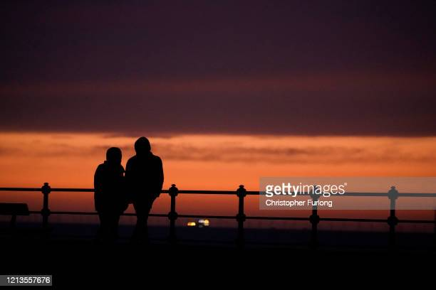 A young couple look out to sea at sunset on March 19 2020 in New Brighton England Coronavirus has spread to over 177 countries in a matter of weeks...