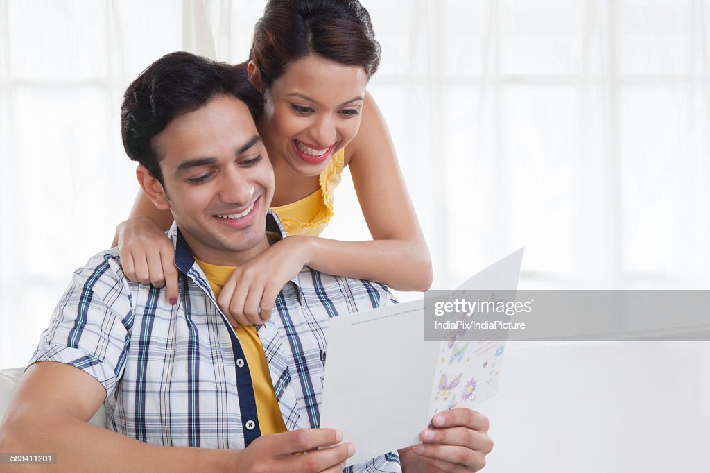 Young couple looking at a greeting card : Stock Photo