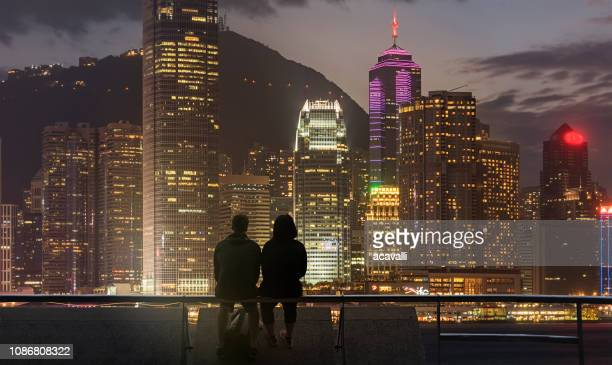 young couple looking at city lights - quayside stock pictures, royalty-free photos & images
