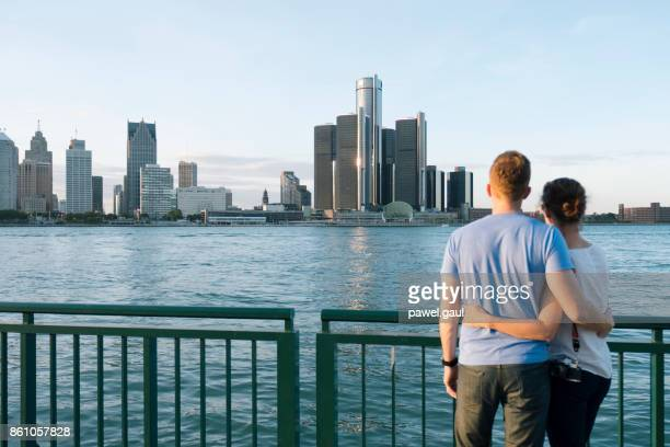 young couple looking at detroit skyline - detroit michigan stock pictures, royalty-free photos & images