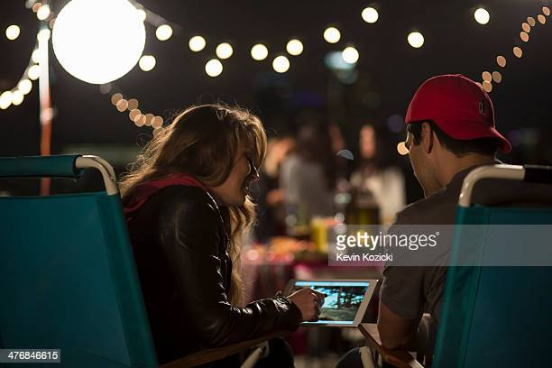 Young couple looking at digital tablet at rooftop barbecue