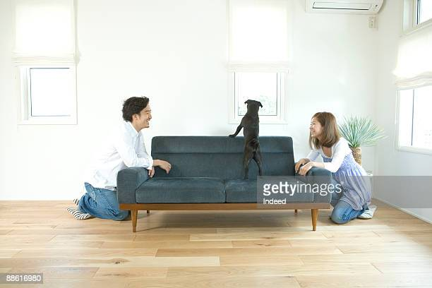 Young couple looking at dog on sofa