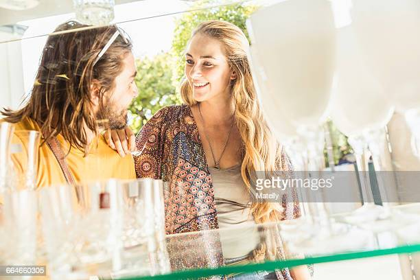 Young couple looking at drinking glasses through shop window, Franschhoek, South Africa