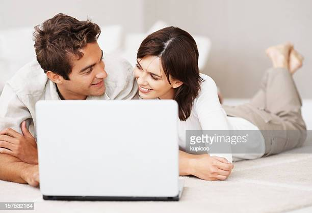 Young couple looking at each other and  using a laptop