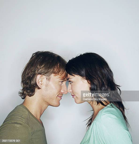 young couple looking at each other, foreheads touching, side view - angesicht zu angesicht stock-fotos und bilder