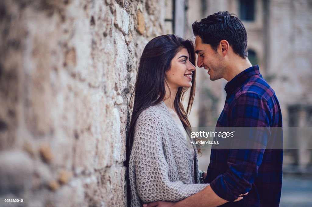 Young couple looking at each other in mediterranean background stock photo