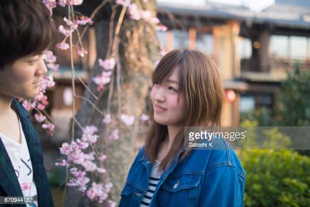 桜の花の近くにお互いを見て若いカップル