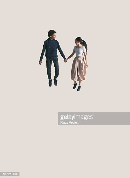 young couple looking at each other, while jumping - volare foto e immagini stock