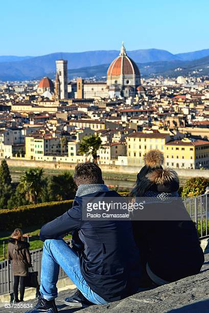 Young couple looking at Florence cityscape seated on steps of Piazzale Michelangelo. Italy