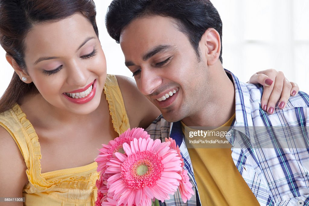 Young couple looking at flowers : Stock Photo