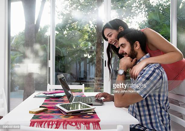 Young couple looking at laptop with excitement.