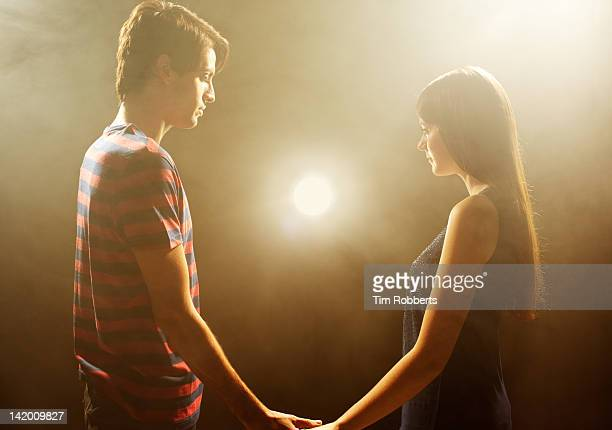 Young couple looking at light, holding hands.