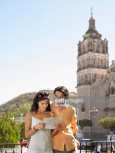 young couple looking at map in plaza de las armas , alamos, mexico - sonora mexico stock photos and pictures