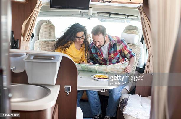 Young couple looking at map inside of caravan