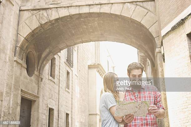 Young couple looking at map outside Valencia Cathedral, Valencia, Spain