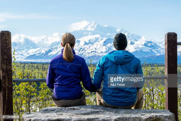 young couple looking at mount denali - heterosexual couple stock pictures, royalty-free photos & images