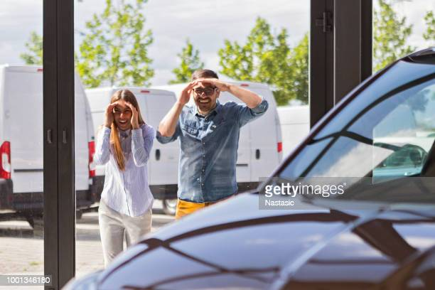 young couple looking at new car in car dealership - desiderio foto e immagini stock