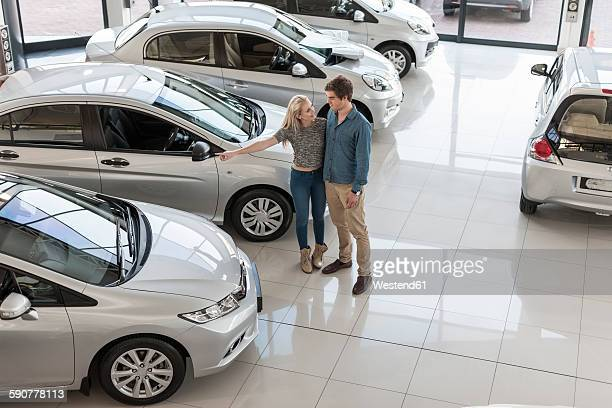 Young couple looking at new cars at car dealership