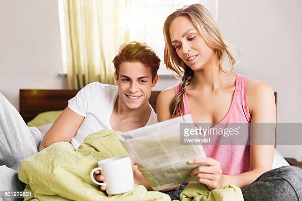 Young couple looking at newspaper while sitting on their bed
