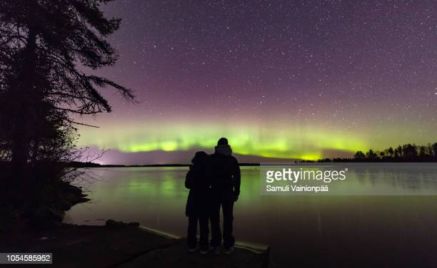 young couple looking at northern lights over lake kuusamo, pohjois-pohjanmaa, finland - aurora borealis stock pictures, royalty-free photos & images