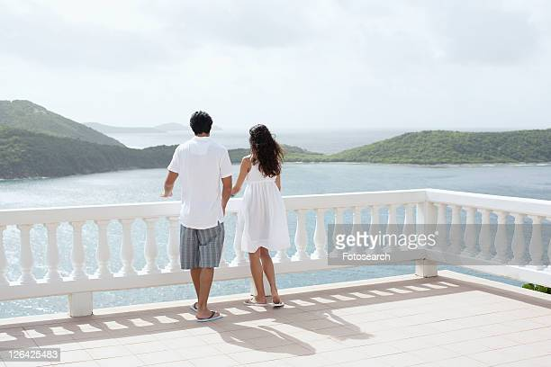 Young couple looking at ocean on balcony, St. John, US Virgin Islands, USA