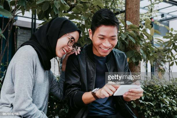 young couple looking at phone - rifka hayati stock pictures, royalty-free photos & images