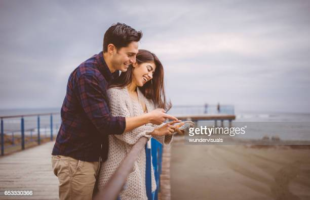Young couple looking at photo on smartphone