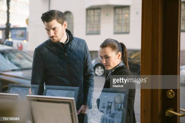 young couple looking at picture frames on display seen from office window - real estate office stock photos and pictures