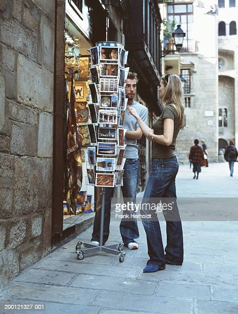 Young couple looking at postcards in shop display