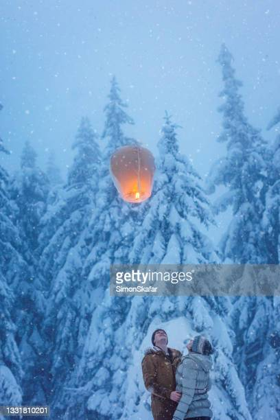 young couple looking at sky lantern on snow - moment of silence stock pictures, royalty-free photos & images
