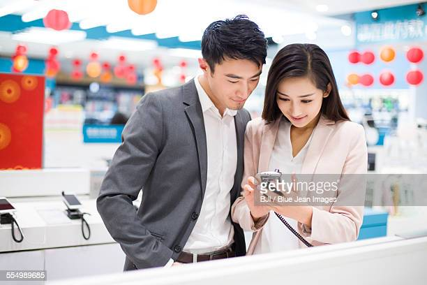 young couple looking at smart phone in electronics store - electronics store stock photos and pictures