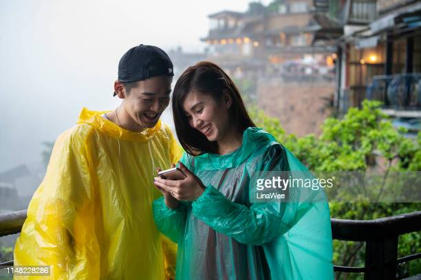young couple looking at smart phone in jiufen, taiwan - poncho stock pictures, royalty-free photos & images