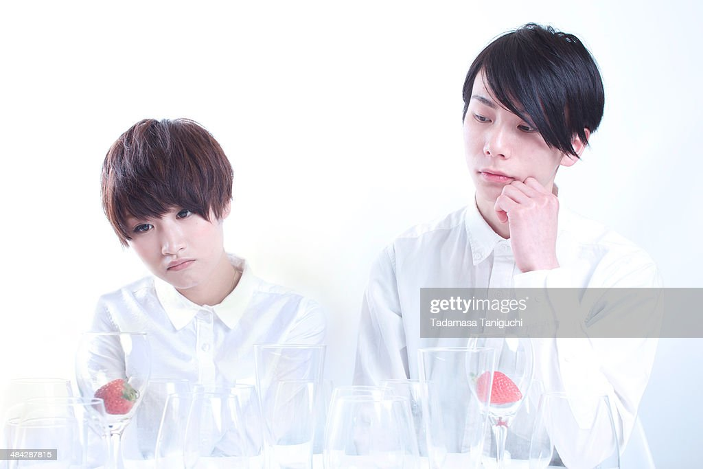 Young couple looking at strawberry in a glass : Stock Photo