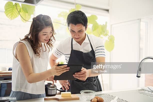 Young couple looking at the recipes in the digital tablet