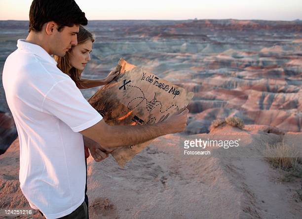 young couple looking at treasure map on barren landscape - three quarter length stock-fotos und bilder