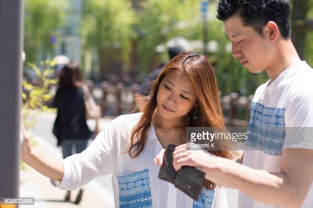 Young couple looking at vending machine to buy a bottle of drink