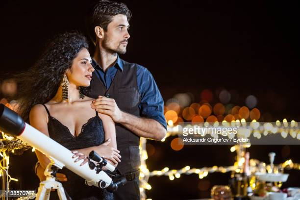 Young Couple Looking Away While Standing By Telescope On Terrace At Night