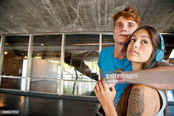 Young couple looking away, woman wearing headphones