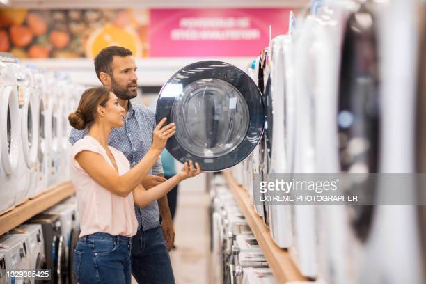young couple looking for a proper drying machine - white goods stock pictures, royalty-free photos & images