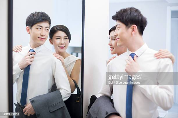 Young couple looking into a mirror before going to work