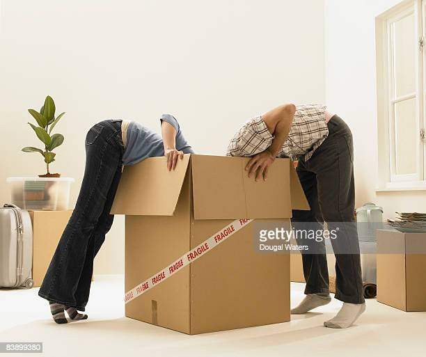 Young couple looking into cardboard box.