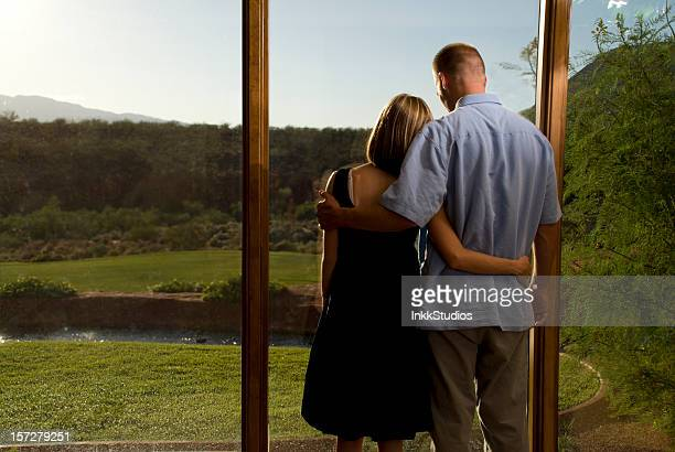 Young couple looking out a window