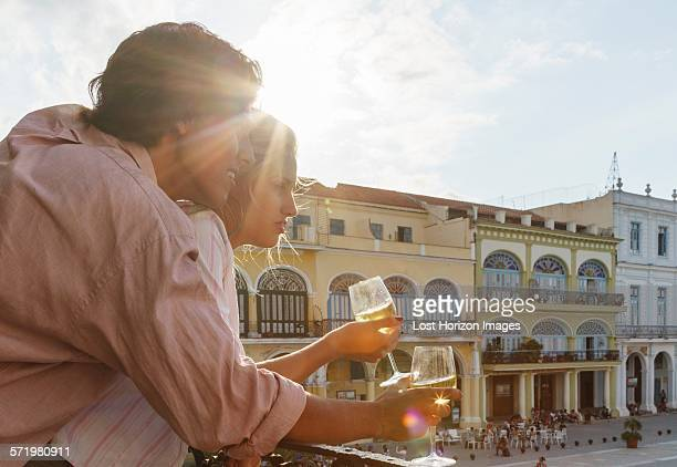 Young couple looking out from restaurant balcony in Plaza Vieja, Havana, Cuba