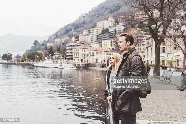 Young couple looking out on lakeside, Lake Como, Italy